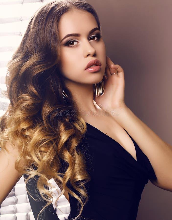 Mooie jonge vrouw met luxueus krullend haar in elegante zwarte kleding royalty-vrije stock afbeelding