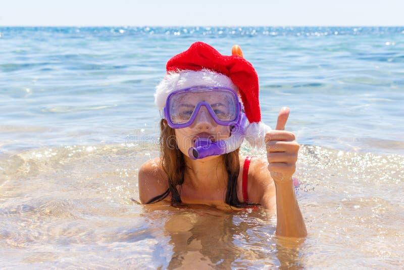 Mooie jonge vrouw met materiaal en Kerstmishoed die bij de overzeese kust snorkelen stock afbeeldingen