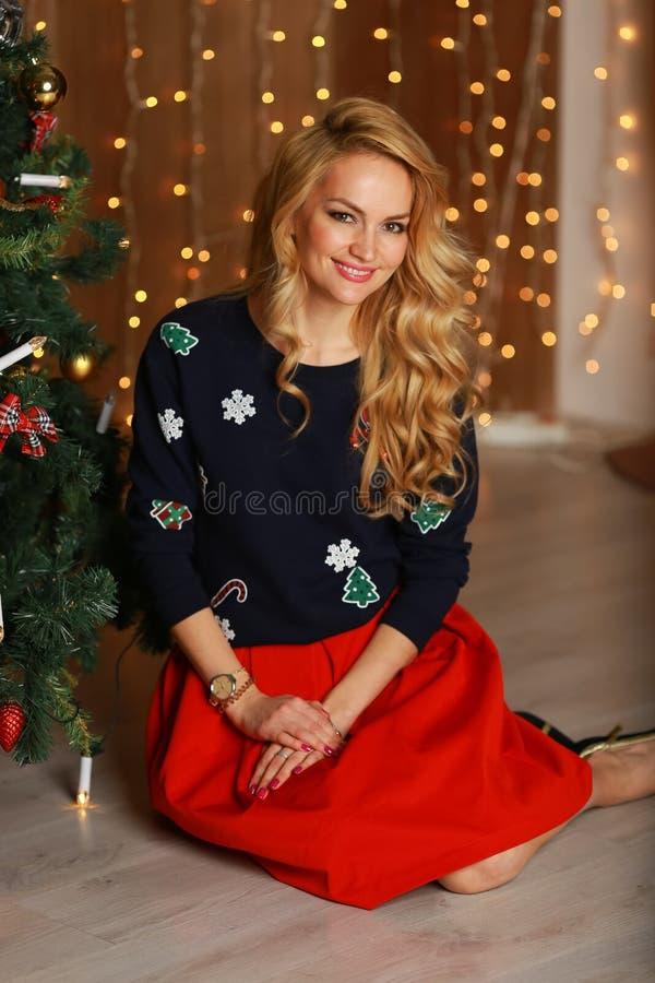 Mooie jonge vrouw met perfecte make-up en modieuze haarzitting op de vloer dichtbij Kerstboom stock afbeelding
