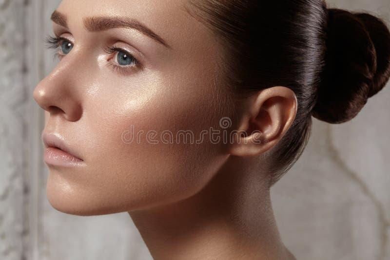 Mooie jonge vrouw met perfecte schone glanzende huid, natuurlijke maniermake-up Glamourportret van model met leuk broodjeskapsel royalty-vrije stock afbeelding
