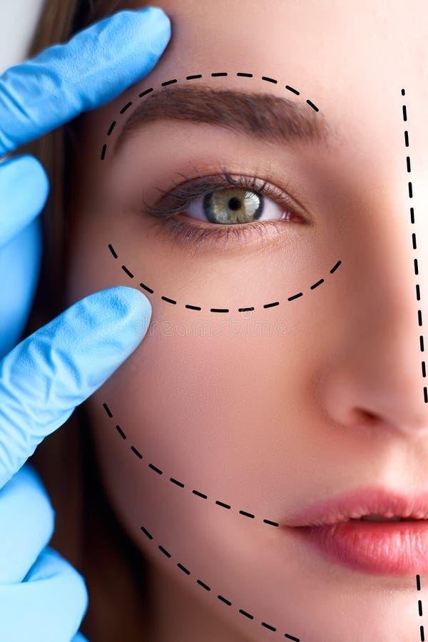 Mooie jonge vrouw met perforatielijnen op haar gezicht v??r plastische chirurgieverrichting De schoonheidsspecialist dient handsc royalty-vrije stock foto's