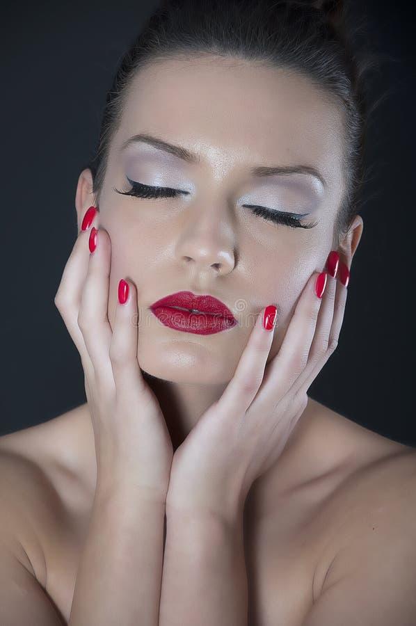 Mooie jonge vrouw met rode spijkers stock afbeeldingen