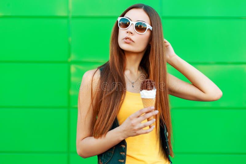 Mooie jonge vrouw met roomijs in zonnebriltribunes royalty-vrije stock fotografie