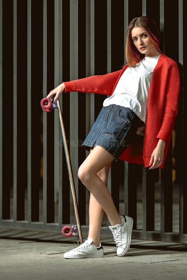 Mooie jonge vrouw met skateboard het stellen stock fotografie