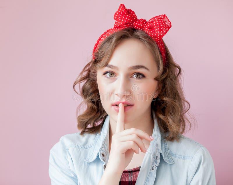 Mooie jonge vrouw met speld-omhooggaand samenstelling en kapsel Studio op roze achtergrond wordt geschoten die stock afbeeldingen