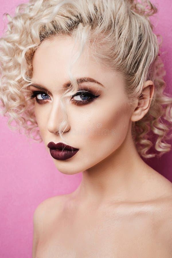 Mooie jonge vrouw met volledige lippen en met blauwe die ogen bij roze achtergrond worden geïsoleerd royalty-vrije stock fotografie