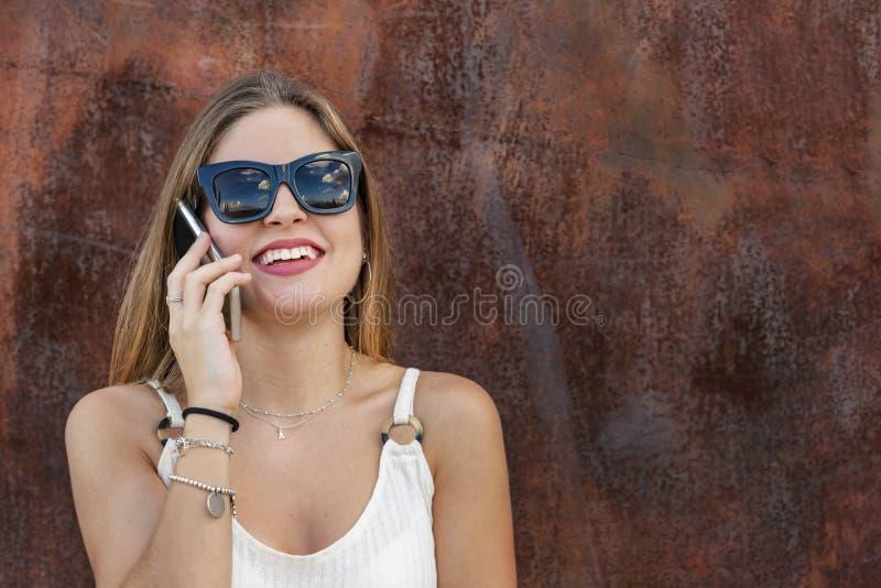 Mooie jonge vrouw met zonglazen die mobiel haar gebruiken stock afbeelding