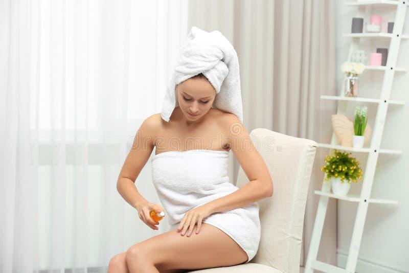 Mooie jonge vrouw na bad die lichaamsolie op huid toepassen royalty-vrije stock afbeeldingen