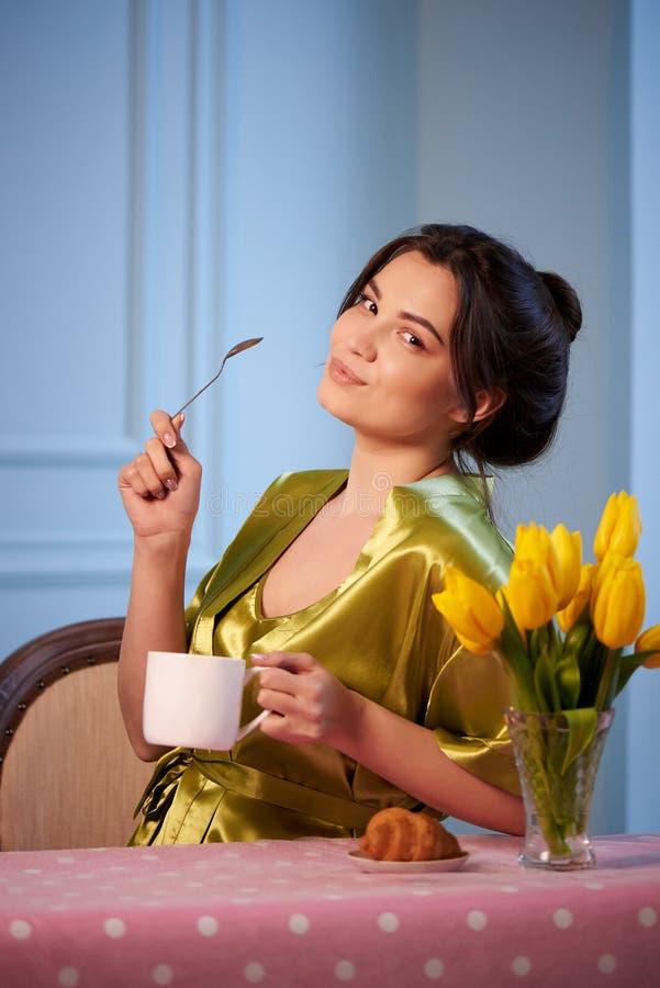 Mooie jonge vrouw in nachtkleding het drinken ochtendkoffie met croissants stock foto