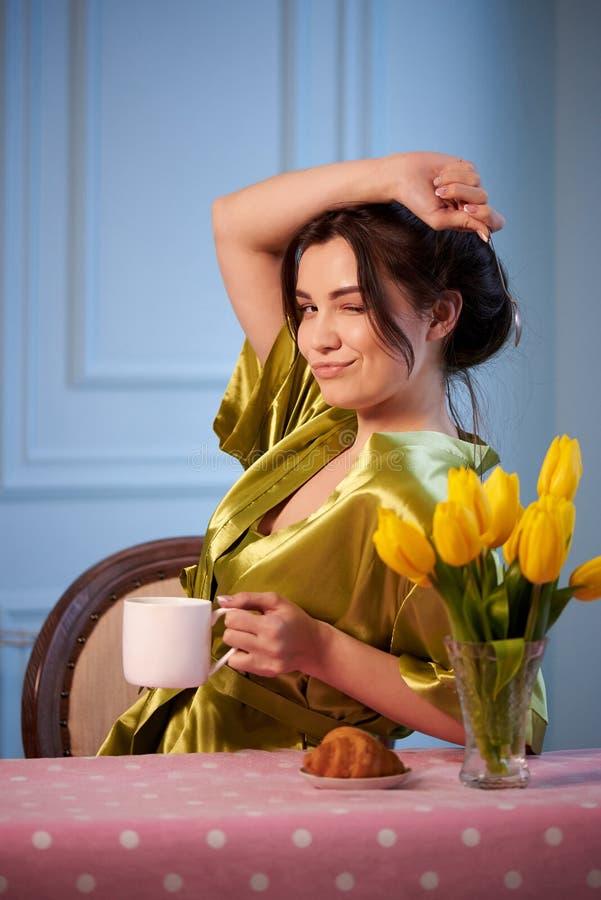 Mooie jonge vrouw in nachtkleding het drinken ochtendkoffie met croissants royalty-vrije stock foto