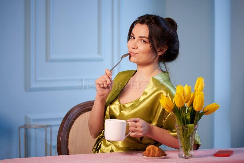 Mooie jonge vrouw in nachtkleding het drinken ochtendkoffie met croissants royalty-vrije stock afbeeldingen