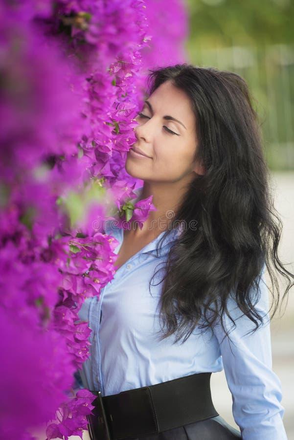 Mooie jonge vrouw op een achtergrond van roze bloemen stock afbeelding