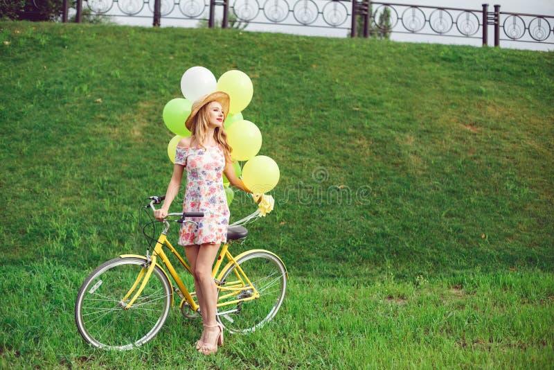 Mooie jonge vrouw op een fiets op een groene gazonachtergrond stock fotografie