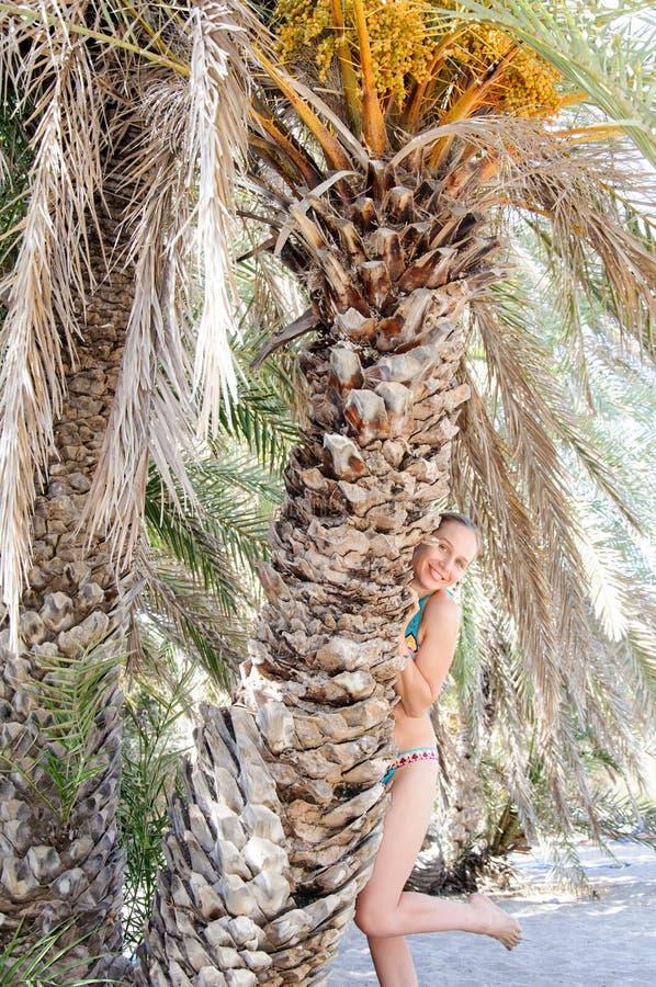 Mooie jonge vrouw op een tropisch strand dichtbij palmen royalty-vrije stock fotografie