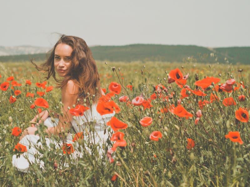 Mooie jonge vrouw op het papavergebied royalty-vrije stock fotografie
