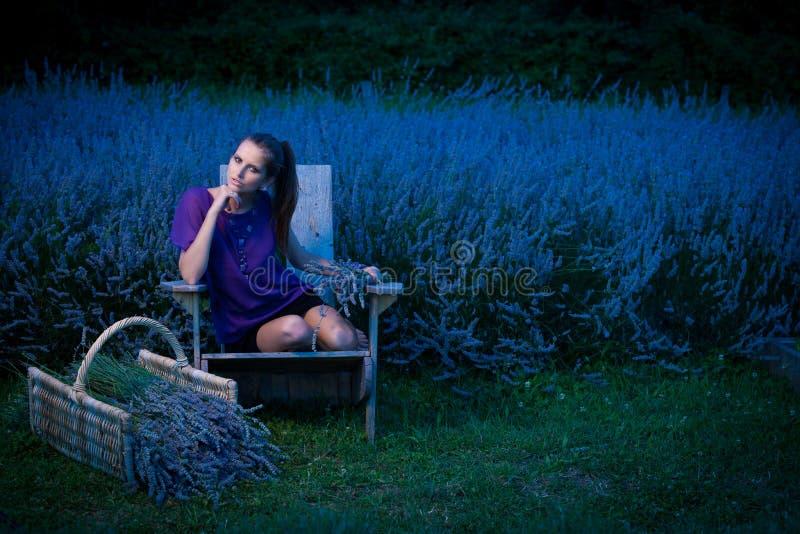 Mooie jonge vrouw op lavandergebied bij schemer - lavandameisje stock afbeelding