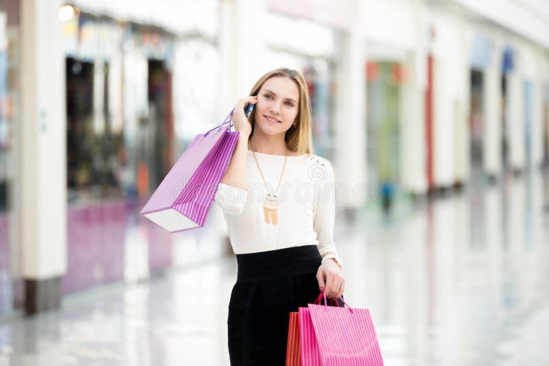 Mooie jonge vrouw op telefoon in winkelcentrum royalty-vrije stock fotografie