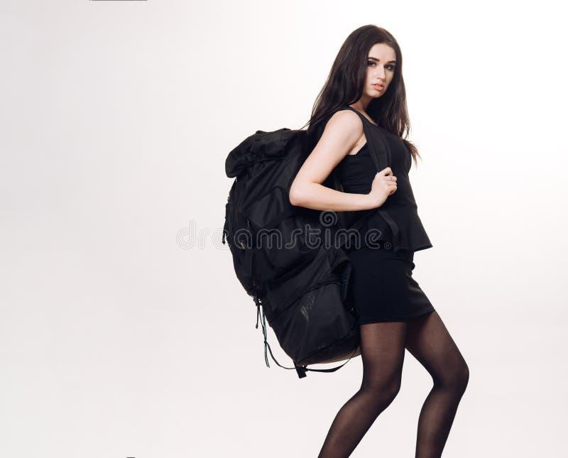 Mooie jonge vrouw in plotseling zwarte kleding het geven grote zware die rugzak op witte achtergrond wordt geïsoleerd r royalty-vrije stock afbeelding