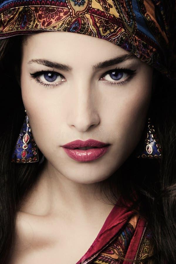 Mooie jonge vrouw portret in oosterse stijl met kleurrijke sjaal en oorringen royalty-vrije stock afbeelding
