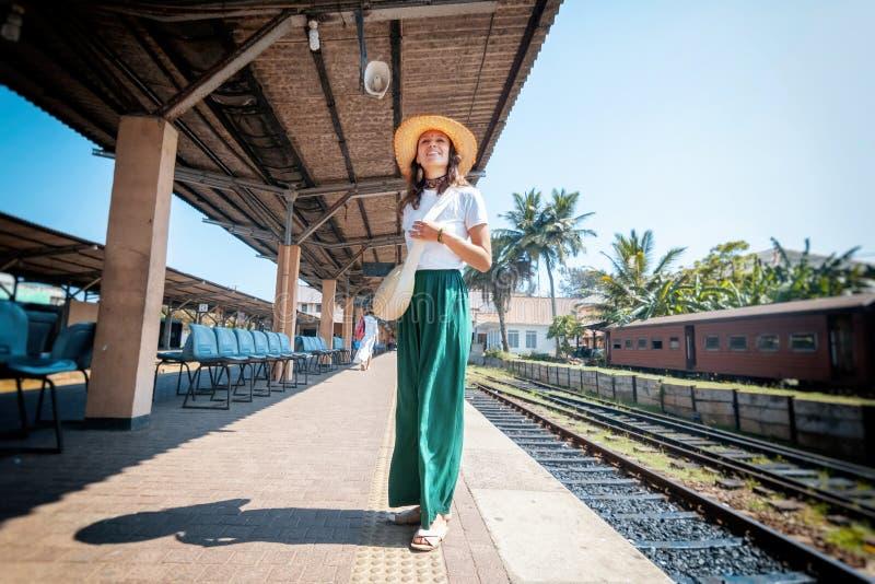 Mooie jonge vrouw in reizigershoed op een spoorwegplatform in Sri Lanka die naar Azië, Ceylon reizen royalty-vrije stock foto