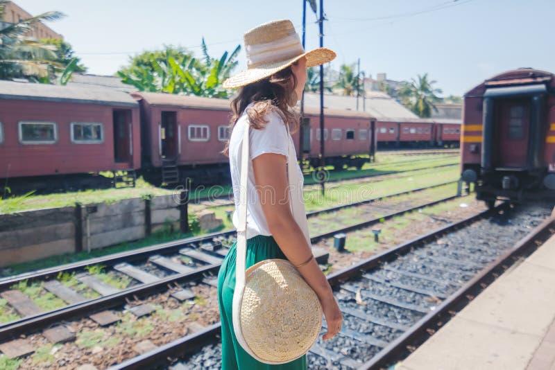 Mooie jonge vrouw in reizigershoed op een spoorwegplatform in Sri Lanka die naar Azi?, Ceylon reizen stock afbeeldingen