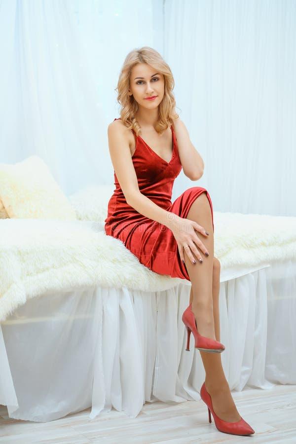 Mooie jonge vrouw in rode kledings liggende zitting op bed royalty-vrije stock fotografie