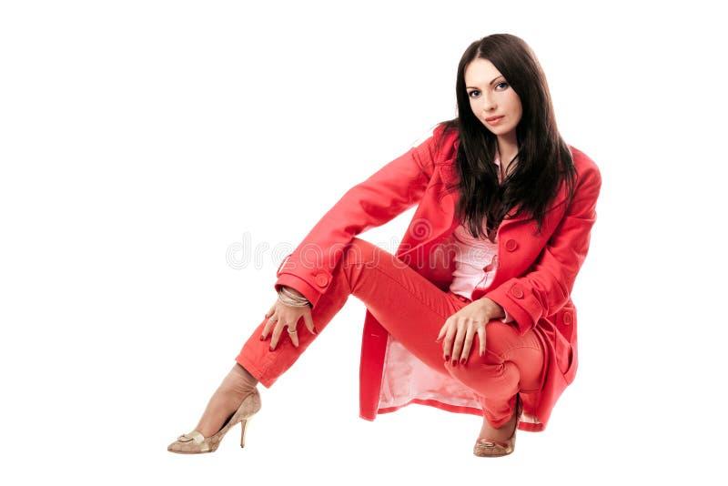 Mooie jonge vrouw in rood kostuum. Geïsoleerdu stock fotografie