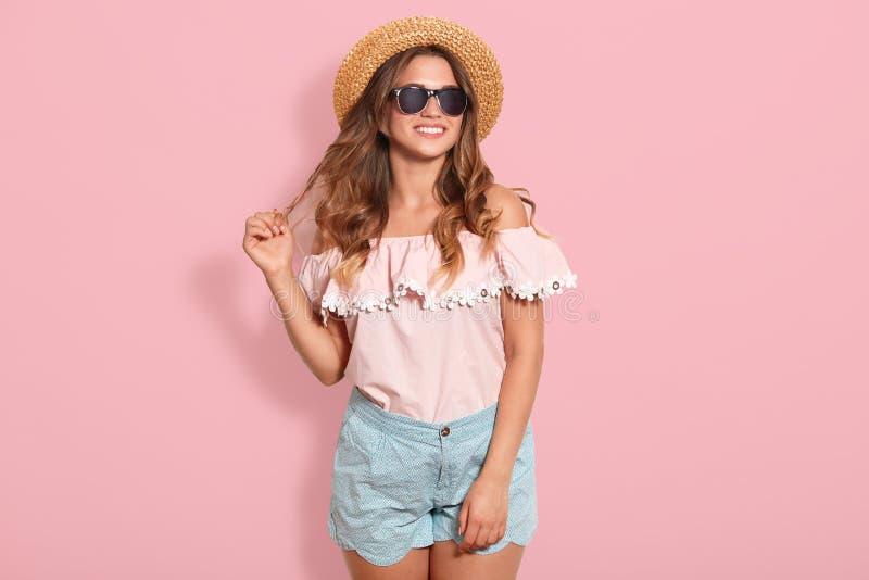 Mooie jonge vrouw in roze de zomerblouse, blauwe kort, zonnebril en zonhoed, trekkend haar haar opzij, zijnd in goede klaar stemm stock foto's