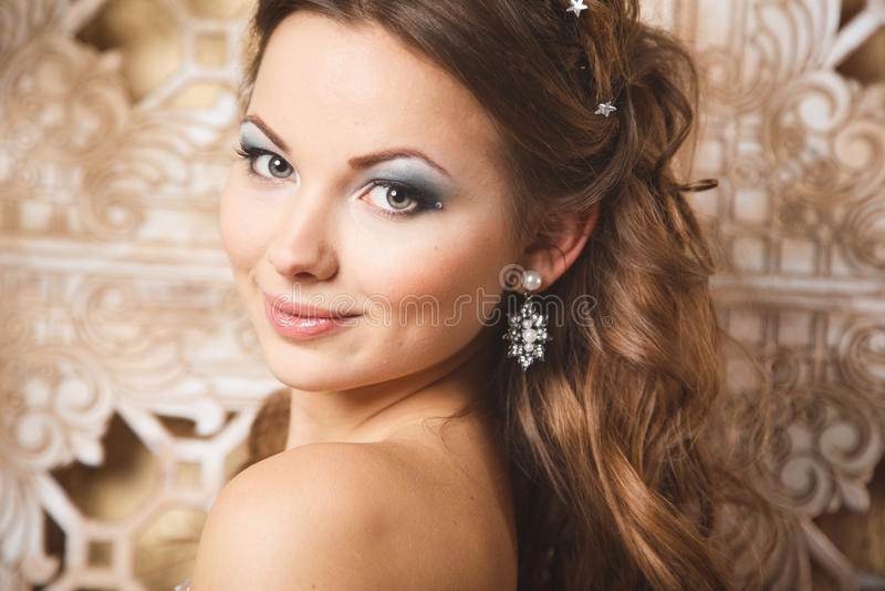 Mooie jonge vrouw in schitterende blauwe lange kleding zoals Cinderella met perfecte samenstelling en haarstijl stock fotografie