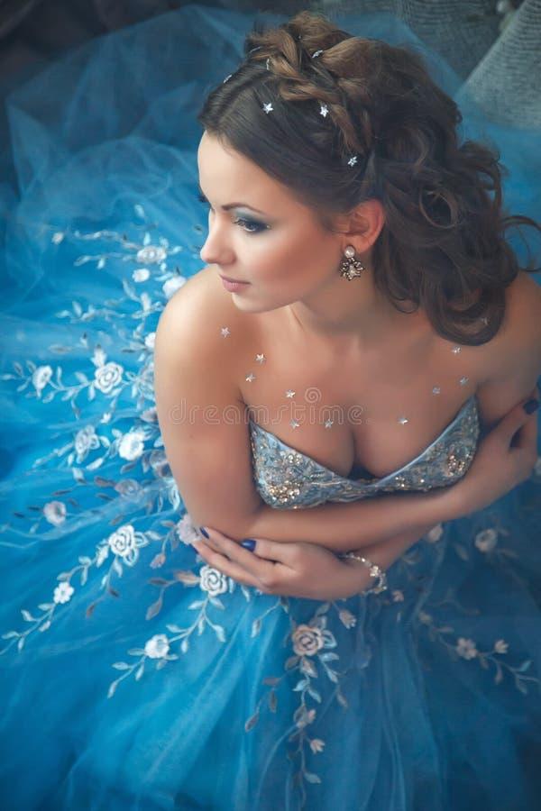 Mooie jonge vrouw in schitterende blauwe lange kleding zoals Cinderella met perfecte samenstelling en haarstijl stock afbeelding