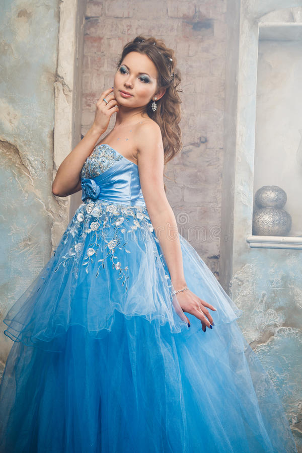 Mooie jonge vrouw in schitterende blauwe lange kleding zoals Cinderella met perfecte samenstelling en haarstijl stock afbeeldingen