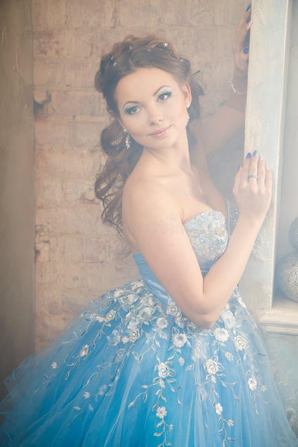 Mooie jonge vrouw in schitterende blauwe lange kleding zoals Cinderella met perfecte samenstelling en haarstijl royalty-vrije stock afbeeldingen