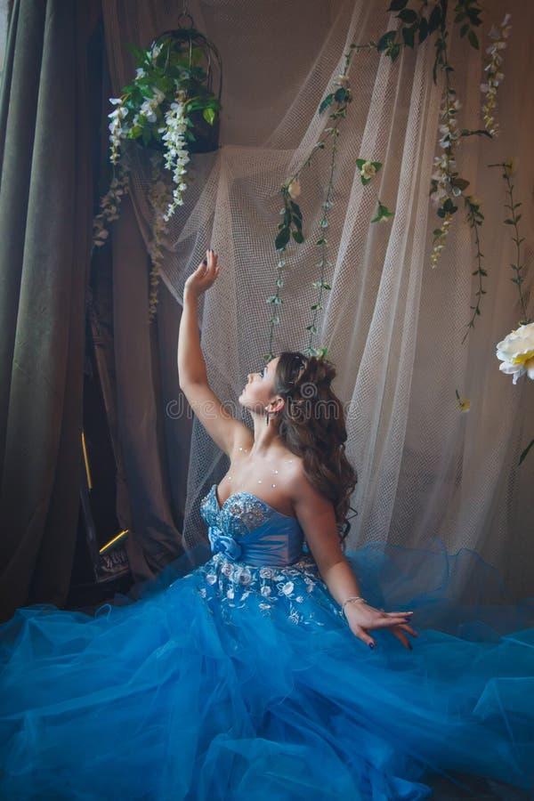 Mooie jonge vrouw in schitterende blauwe lange kleding zoals Cinderella met perfecte samenstelling en haarstijl royalty-vrije stock fotografie