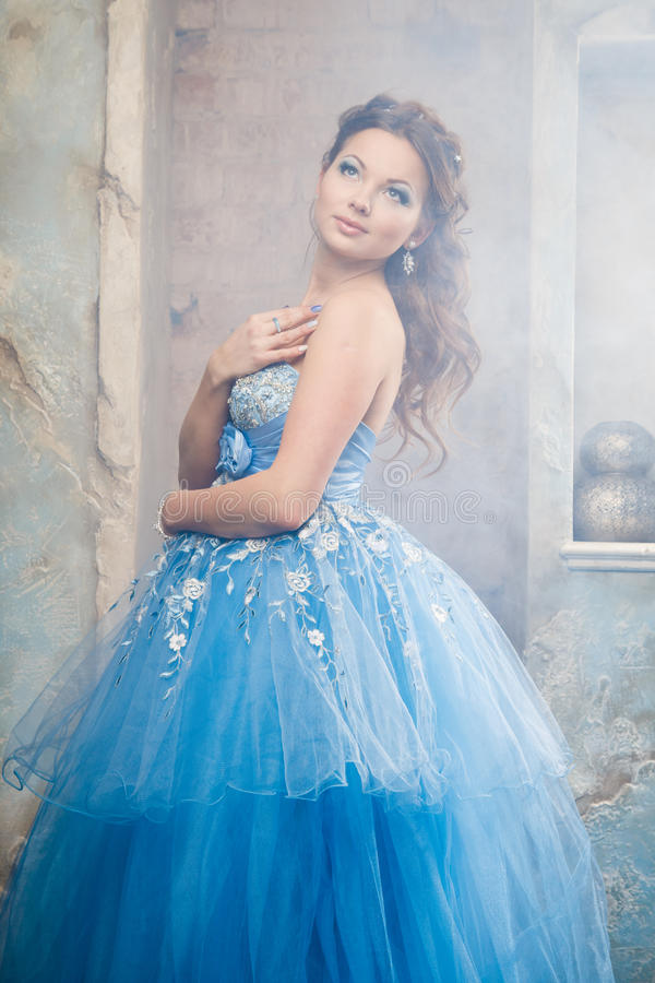 Mooie jonge vrouw in schitterende blauwe lange kleding zoals Cinderella met perfecte samenstelling en haarstijl stock foto
