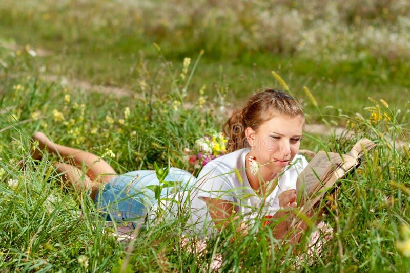 Mooie jonge vrouw-student die een boek lezen die op het gras liggen Mooi meisje in openlucht in zomer royalty-vrije stock fotografie
