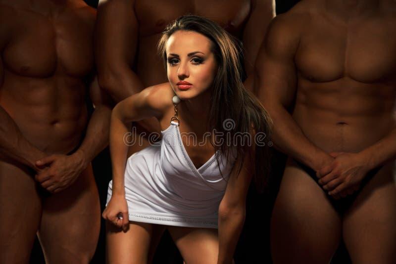 Mooie jonge vrouw tegen drie atleten stock afbeelding