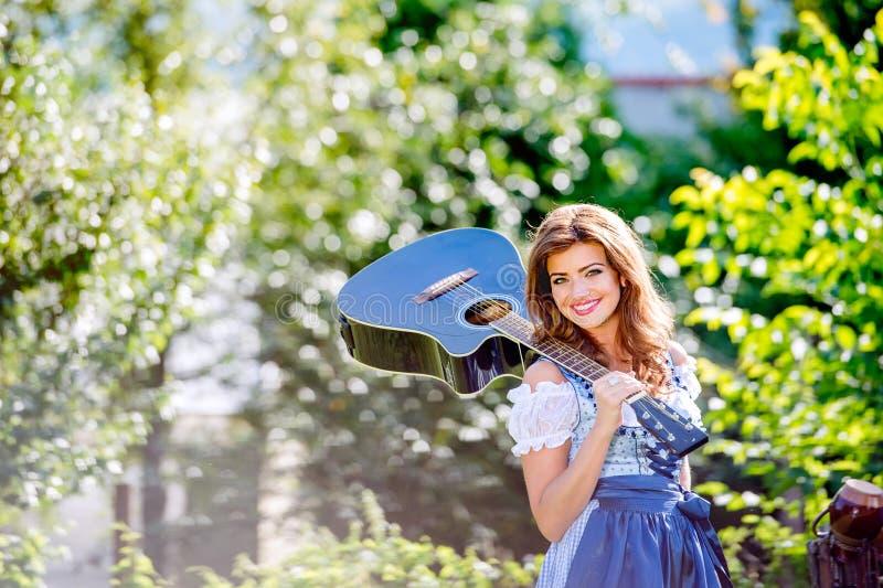 Mooie jonge vrouw in traditionele Beierse kledingsholding guit royalty-vrije stock foto