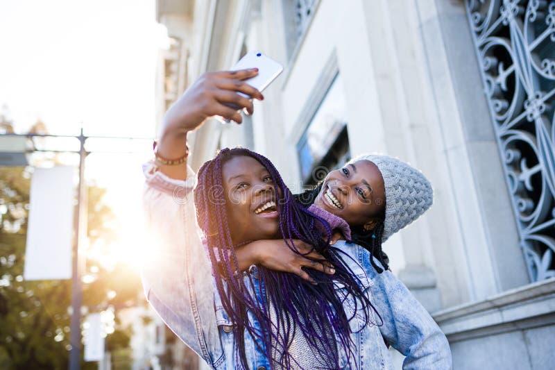 Mooie jonge vrouw twee die mobiele telefoon in de straat met behulp van stock afbeeldingen
