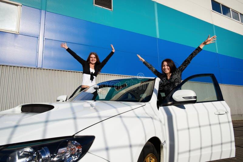 Mooie jonge vrouw twee en witte sportwagen stock foto