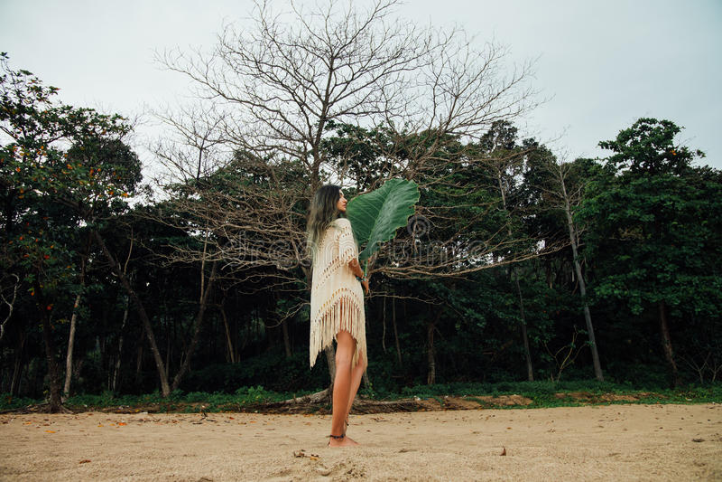 Mooie jonge vrouw in uniformjas op strand met grote blad tropische palm royalty-vrije stock afbeelding