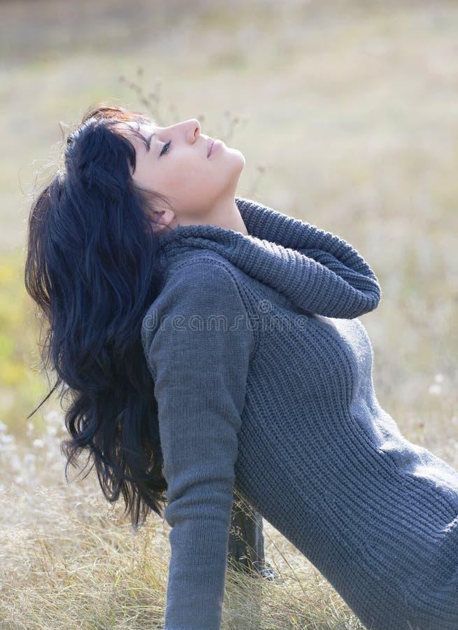 Mooie jonge vrouw voor dalingsachtergrond stock afbeelding