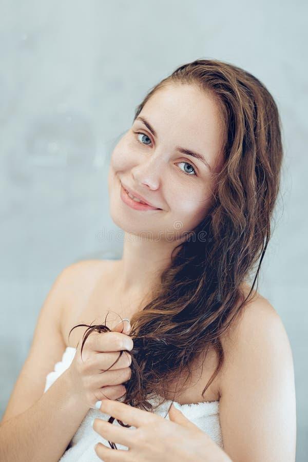 Mooie jonge vrouw wat betreft haar nat haar met handen en het glimlachen terwijl status voor de spiegel in badkamers royalty-vrije stock afbeelding