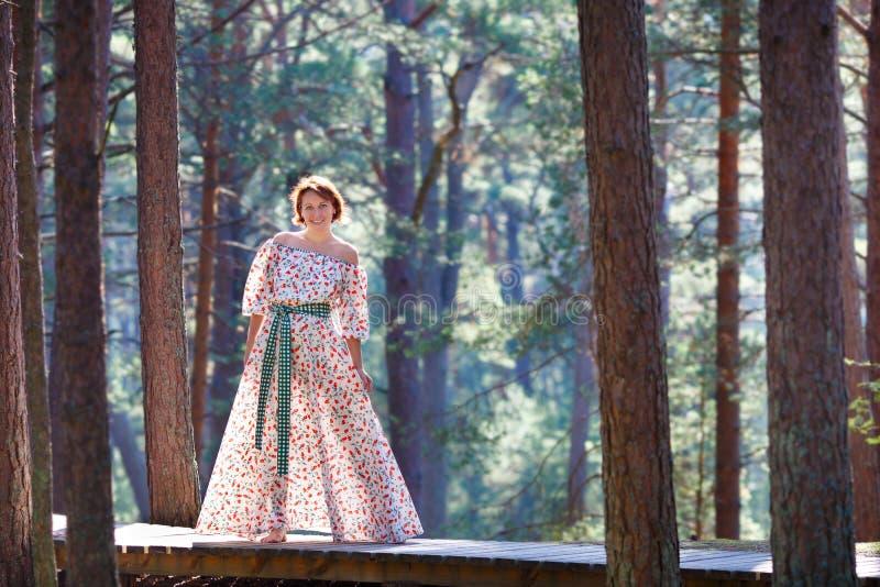 Mooie jonge vrouw in wit en het lange kleding stellen op het bos stock fotografie