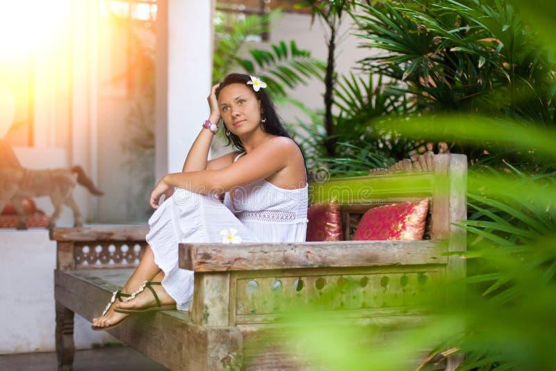 Mooie jonge vrouw in witte kleding die op uitstekende bank in tuin rusten Reis en de zomerconcept stock foto's