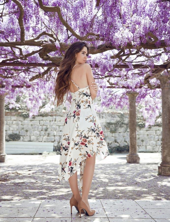 Mooie jonge vrouw in witte kleding over de boog van de wisteriatunnel royalty-vrije stock foto's