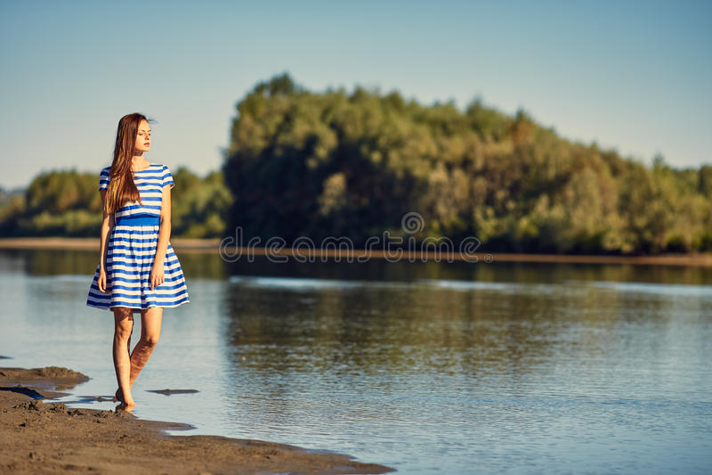 Mooie jonge vrouw in zeemans het gestreepte kleding stellen stock afbeeldingen