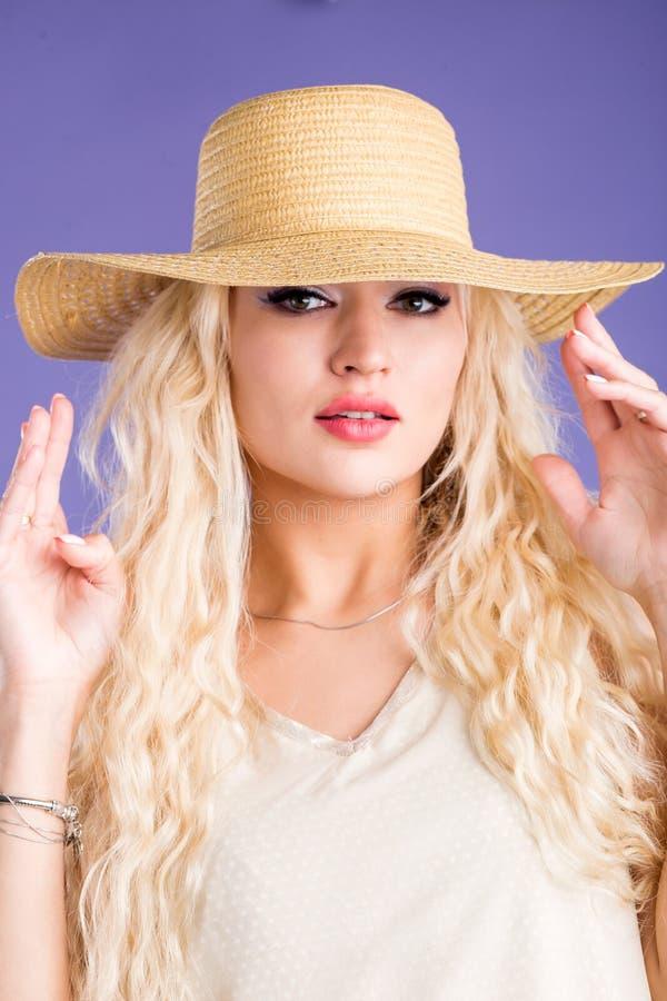Mooie jonge vrouw in zonhoed op purpere achtergrond stock fotografie