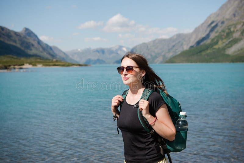 mooie jonge vrouw in zonnebril met rugzak die zich dichtbij majestueus Gjende-meer, Besseggen-rand, het Nationale Park van Jotunh stock foto