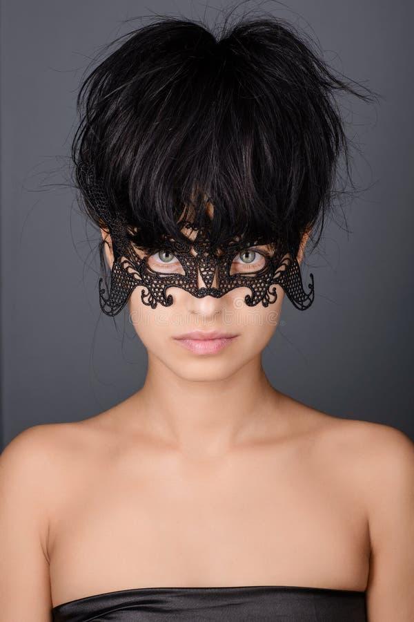 Mooie jonge vrouw in zwart geheimzinnig kant Venetiaans masker royalty-vrije stock afbeelding