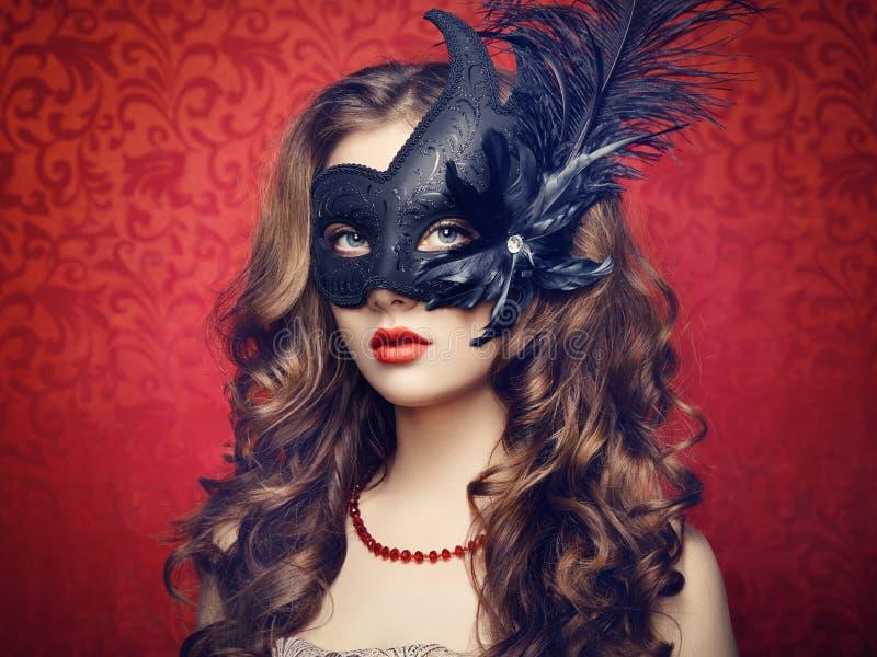 Mooie jonge vrouw in zwart geheimzinnig Venetiaans masker royalty-vrije stock afbeeldingen